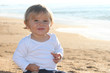 Happy blond baby playing at the beach