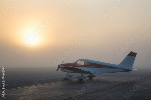 Fotografie, Obraz  Beautiful foggy sunrise at the Airport with an Airplane parked at the apron