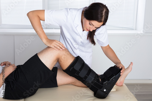 Fotografía Orthopedist Adjusting Walking Brace On Patient's Leg