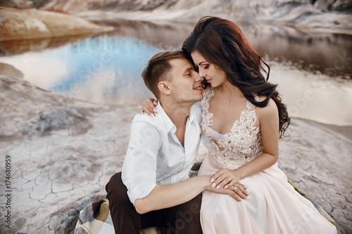 Plakat Piękna para zakochanych całowanie i przytulanie siedzi na skałach wśród bajecznych gór. Czerwone jezioro krwi. Mężczyzna i kobieta w pięknej sukni ślubnej. Długa lekka letnia sukienka na ciele kobiety