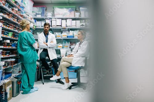 Fototapeta Hospital staff discussing medication in the pharmacy obraz na płótnie