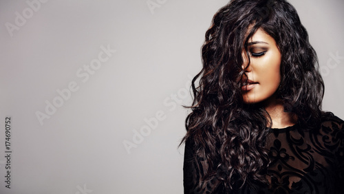 Zmysłowa kobieta z lśniącymi kręconymi włosami