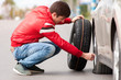 Young driver changing tyre wheel after breakdown