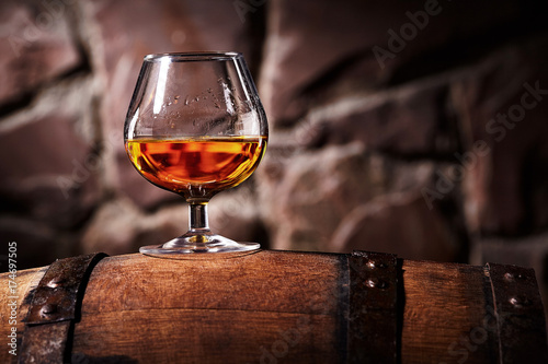 Photo Glass of cognac on the old wooden barrel