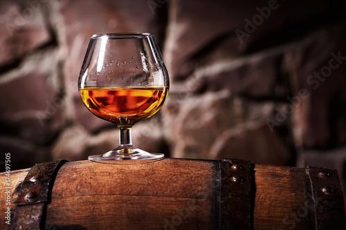 Cuadros en Lienzo Glass of cognac on the old wooden barrel