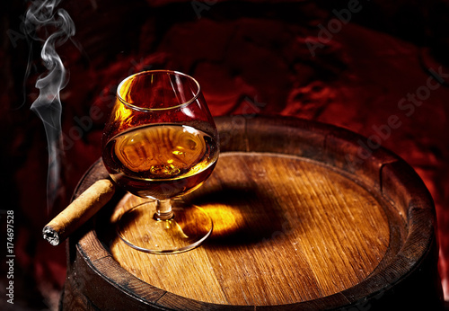 Cognac and Cigar on old oak barrel.Red stone background