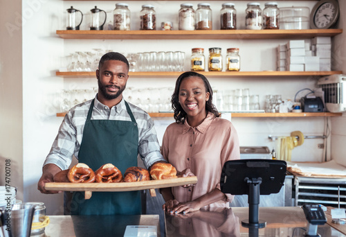 Carta da parati Smiling African entrepreneurs with baked goods behind their bakery counter