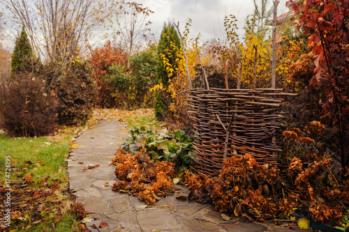 Fotobehang Tuin Walking in november garden. Late autumn view with rustic fence and stone pathway
