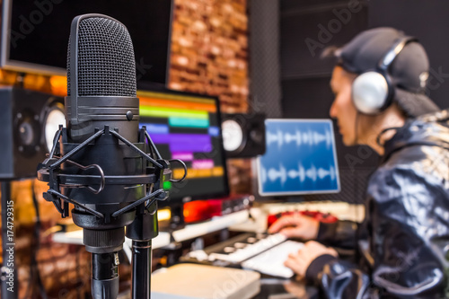 Fotografía studio condenser microphone on sound engineer working in control room background