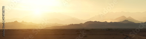 Foto auf Leinwand Beige Valley in the desert with mountains at sunset