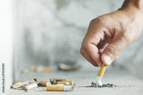 Photo  Hand putting out a cigarette,cigarette butt on Concrete floor, bare cement