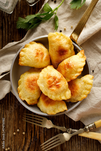 Baked dumplings stuffed with curd cheese and potatoes in a pan, top view