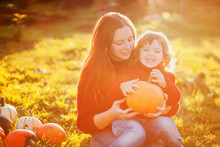 Mother And Child With Pumpkin Harvest.