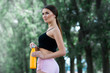 Beautiful girl getting ready for jogging in the park. With thermos bottle in hand.