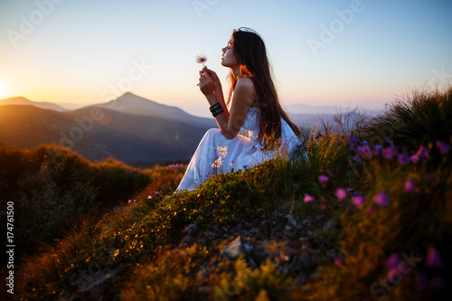 Photo sur Toile Marron chocolat A girl sits on the edge of the cliff and looking at the sun valley and mountains. Woman sitting on mountain top and contemplating the sunset. Young woman in long white dress