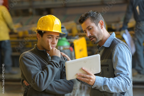 Fotografía  foreman explaining to employee with tablet
