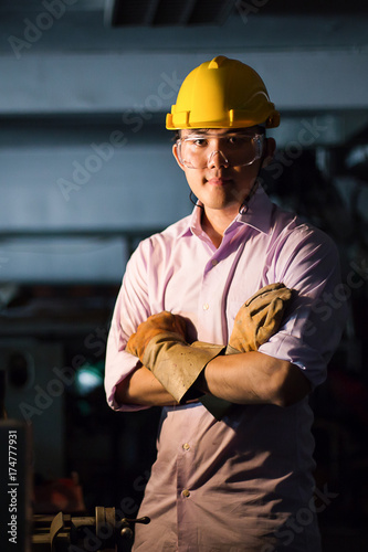 Photo Portrait of young adult experienced industrial asian worker over industry machin