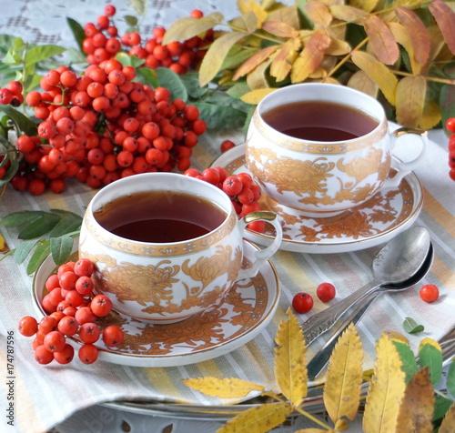 czarna-herbata-w-dwoch-ozdobnych-filizankach-oraz-swieza-jarzebina