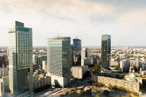 Fototapeta Nowoczesne wieżowce z odbicia okna w centrum Warszawy, widok z Pałacu Kultury i Nauki w ciepłym, słonecznym świetle dziennym