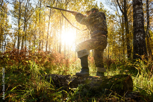 A hunter with a gun in the forest at dawn.
