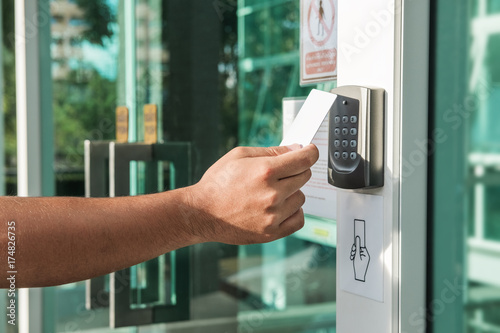 Photo  Hand using security key card scanning to open the door to entering private building