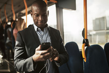 Smiling African Businessman Listening To Music During His Morning Commute