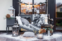 Outdoor New Year Decoration. Wooden Bench With Plaid, Candles, Pillows And Snow. Christmas And New Year Concept. Cozy Home Decor. Rustic Style. Window And Door On Background.