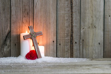 White Holiday Candles In Snow By Red Flower And Wood Cross With Rustic Wooden Background