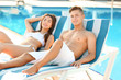 Happy young couple resting near swimming pool at resort