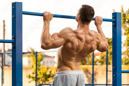 Plakat Mięśniowy mężczyzna robi ciągnieniu up na horyzontalnym barze, pracującym out. Silne fitness mężczyzna wyciągając, pokazując, na zewnątrz