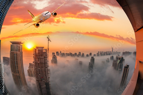 Staande foto Midden Oosten Plane is flying over Dubai against colorful sunset in United Arab Emirates