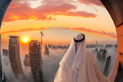 Photo  Arabian man is watching Dubai marina in Dubai, United Arab Emirates