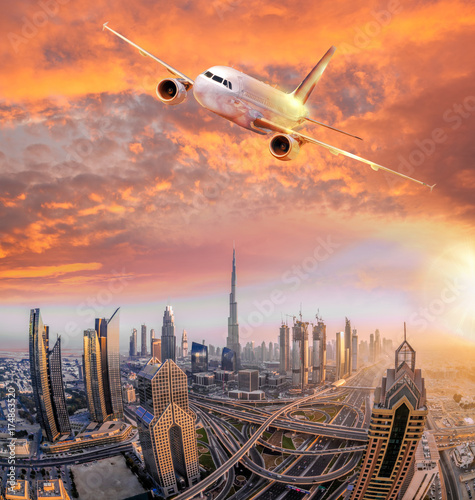 Fotobehang Midden Oosten Airplane is flying over Dubai against colorful sunset in United Arab Emirates