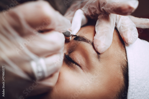 Photo Closeup of a beautician hands applying japanese method of drawing on eyebrows to model