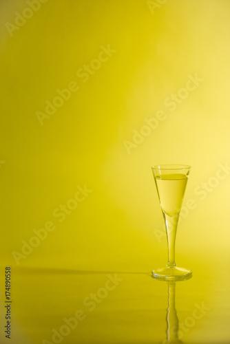 Fotografie, Obraz  Yellow liquid in aperitif glass on yellow background.