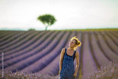 Fotografie, Obraz  girl farmer in overalls bent her head under the rays of the evening sun, standin