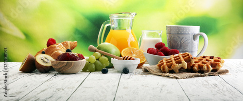 Obraz na płótnie Breakfast served with coffee, orange juice, croissants and fruits