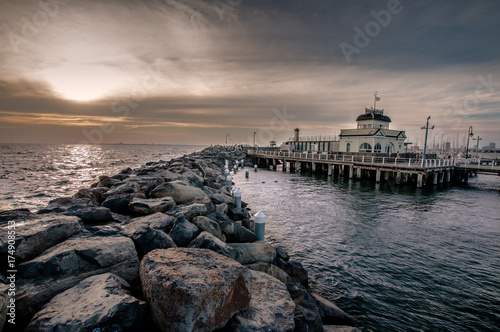 St kilda Pier and kiosk in Melbourne Australia at dusk on a cloudy day.