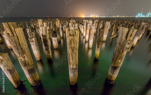 Wooden Princes Pier at night in Melbourne Australia with green water and myst in the background.