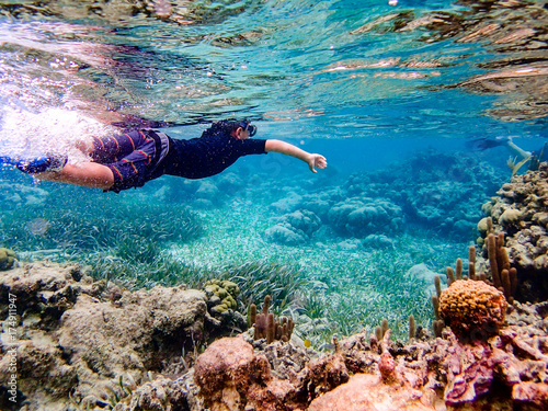 Underwater image of boy snorkeling through coral reef near Ambergris Caye, Beliz Wallpaper Mural