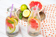 Infused flavored water with fresh fruits on white wooden background.Refreshing summer homemade detox water