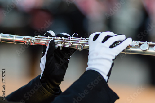 Fotografia, Obraz  gloved hands of a flute player in a marching band