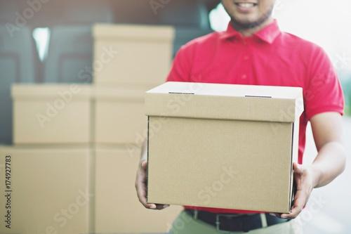 Smiling young male postal delivery courier man in beside of cargo van delivering package Tapéta, Fotótapéta