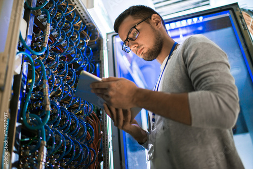 Low angle  portrait of young man using digital tablet standing by server cabinet Wallpaper Mural