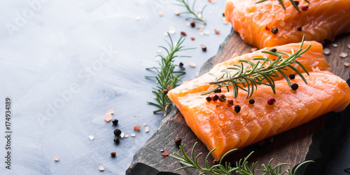 Raw salmon pieces on wooden board with herbs, salt and spices