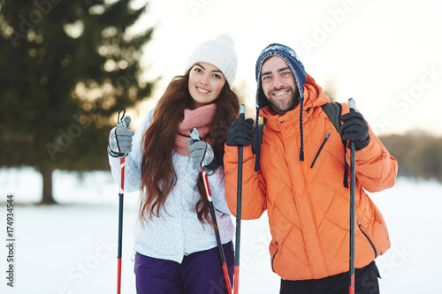 Tuinposter Wintersporten Young sweethearts skiing in forest together on winter weekend