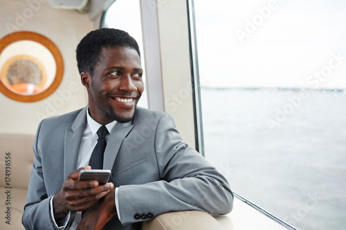 Fotografie, Obraz  Happy African-american businessman with smartphone sitting by steamer window and