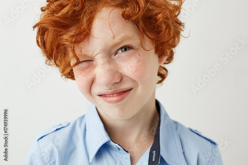 Close up of funny ginger boy with freckles and red cheeks screw up eye because of bright lightning in school class.
