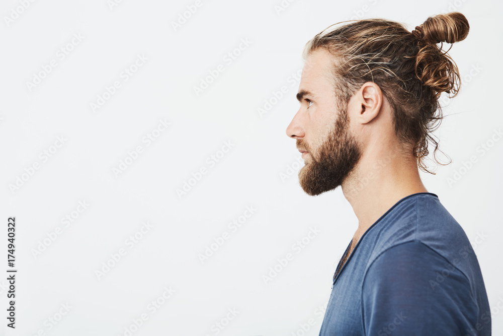 Fototapeta Close up of good-looking bearded hipster guy with hair in bun, in blue t-shirt standing in profile, looking aside, posing for photo.