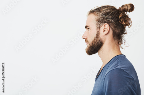 Fototapeta Close up of good-looking bearded hipster guy with hair in bun, in blue t-shirt standing in profile, looking aside, posing for photo. obraz